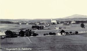 Eugendorf gegen Norden, um 1930: Im Vordergrund links der Strasserwirt, im Mittelgrund die Trasse der ehemaligen Salzkammergutlokalbahn mit dem kleinen Bahnhofsgebäude (Reproduktion: SLA)